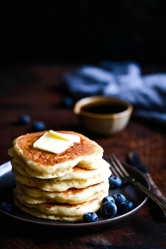A stack of buttermilk pancakes topped with a pat of butter