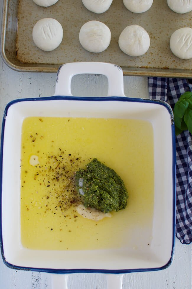 a baking dish with melted butter, pesto, salt and pepper