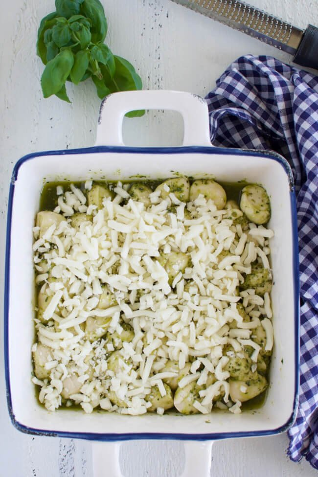 a baking dish with pesto coated rolls sprinkled with grated mozzarella cheese