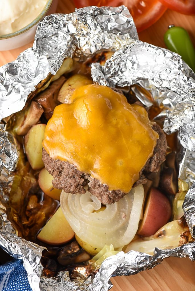 a cheese burger patty on top of cooked onions, carrots and potatoes