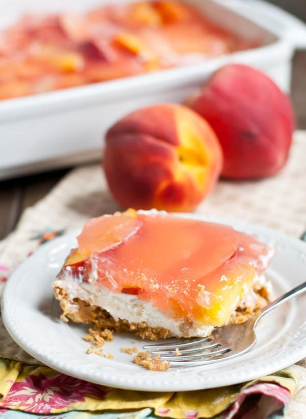 a square of no bake dessert with crumb crust, cream cheese layer, and peach gelatin layer