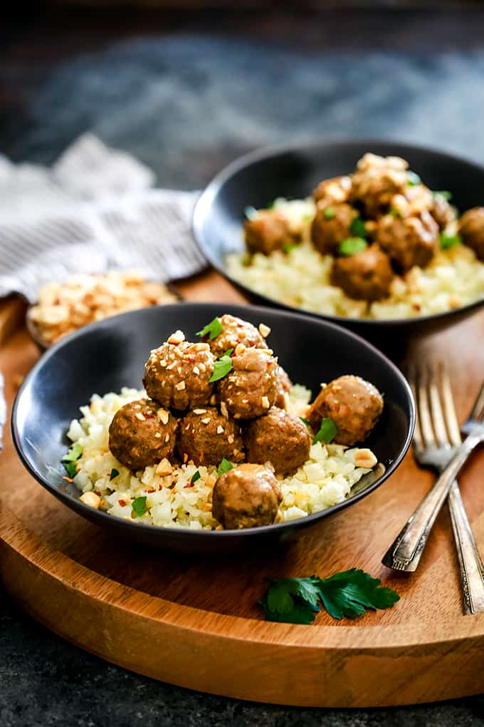 Two black bowls with rice topped with meatballs