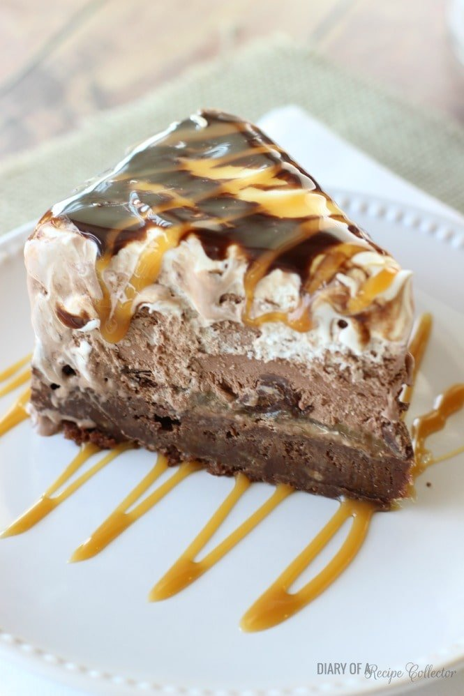 a wedge ice cream cake with layers of brownie, ice cream, whipped cream, and hot fudge topping