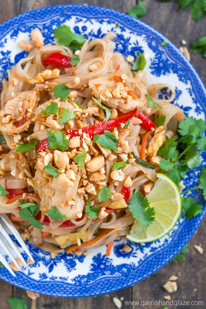 a plate with thai chicken, lime slices, and noodles