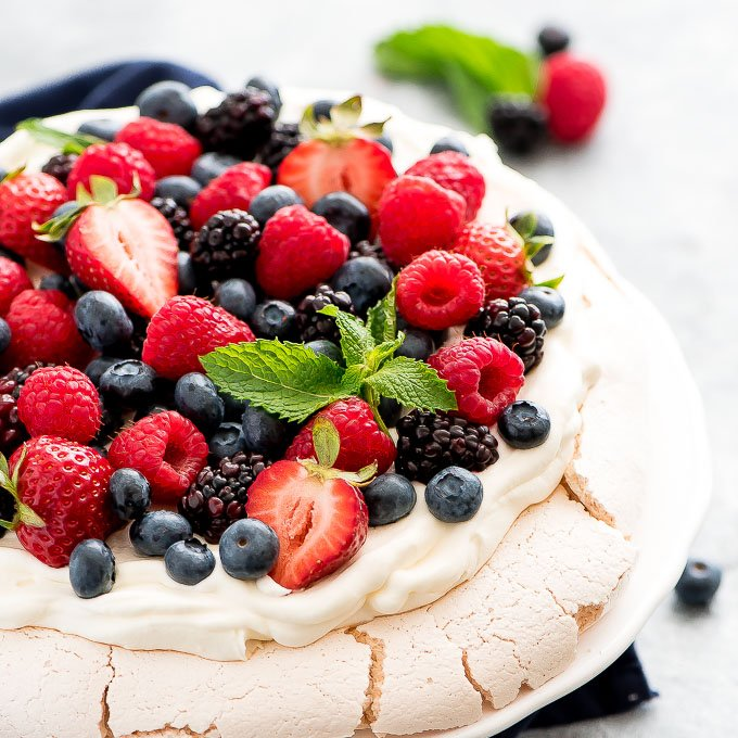 a dessert on a plate topped with fresh blueberries, blackberries, and strawberries