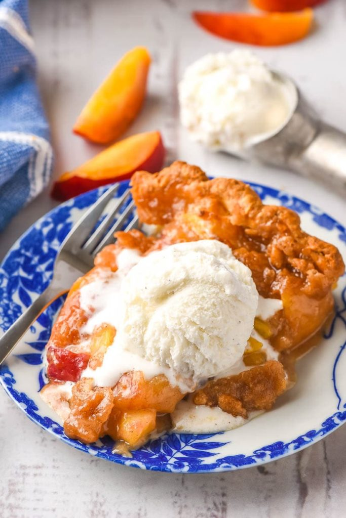 a wedge of peach pie topped with a crumble topping and vanilla ice cream