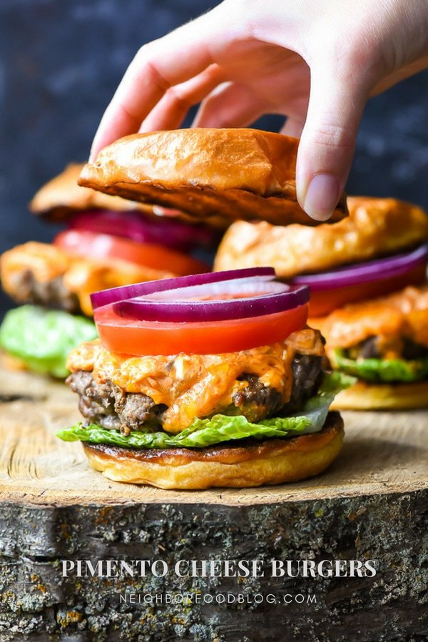a burger with lettuce, cheese, red onion, sliced tomato, and a bun top