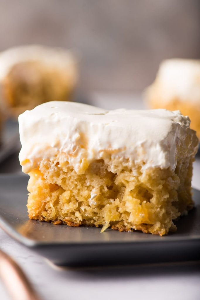 a piece of pineapple cake with whipped topping