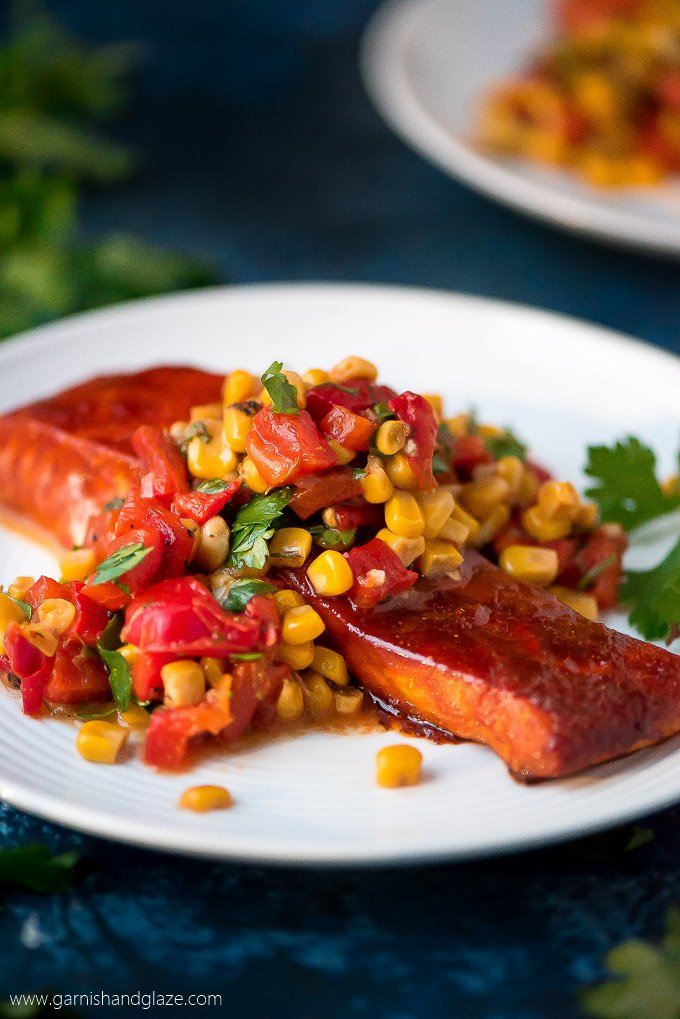 a slice of salmon glazed in a sauce and topped with corn relish