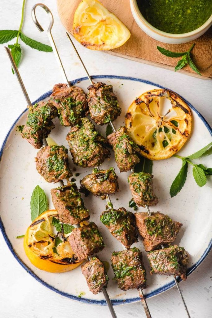 skewers with grilled steak covered with and herb sauce and lemon slices on the sides