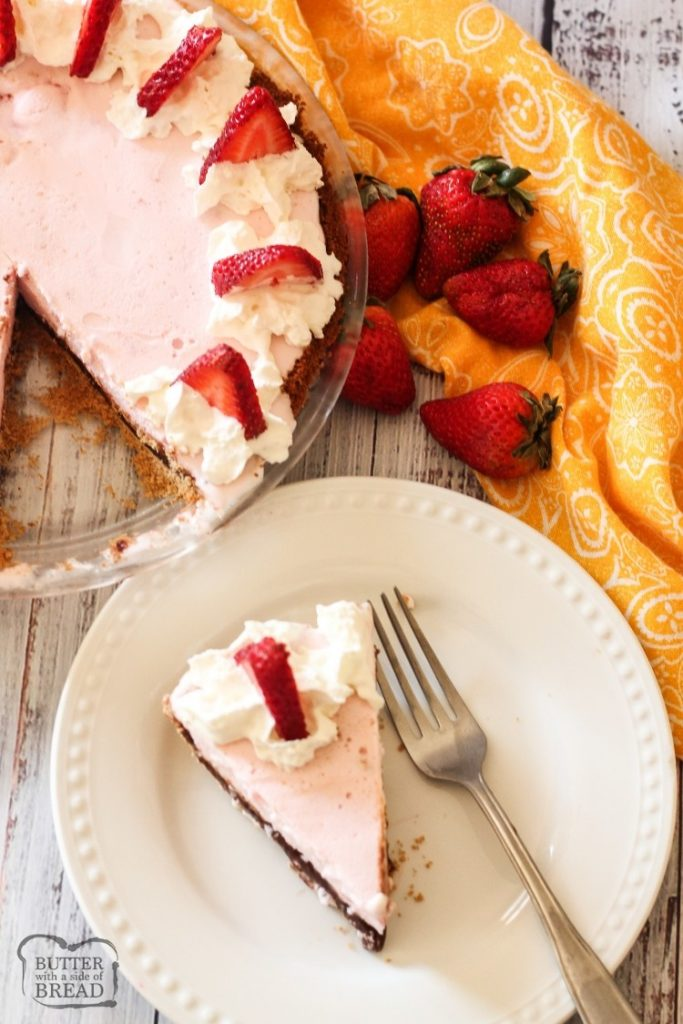 a wedge of pink pie with whipped cream and a strawberry on a white plate, with a pie pan of pie