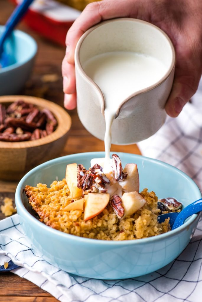 a bowl of baked oatmeal topped with diced apples and walnuts