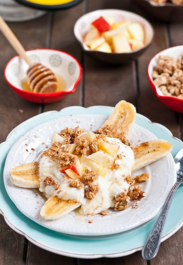 a plate with yogurt banana split topped with granola and diced apples