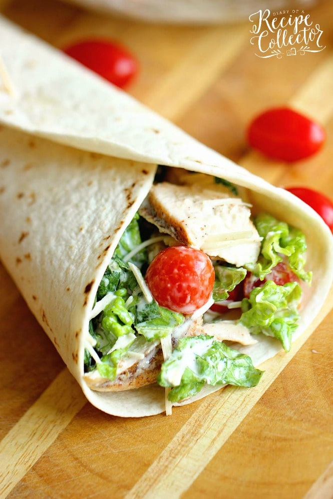 a wrap filled with cherry tomatoes, lettuce, sliced chicken, and grated cheese