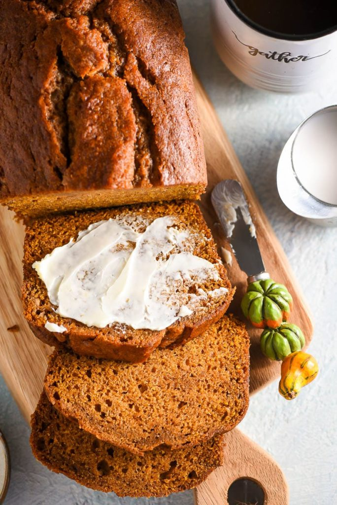 sliced pumpkin bread spread with butter