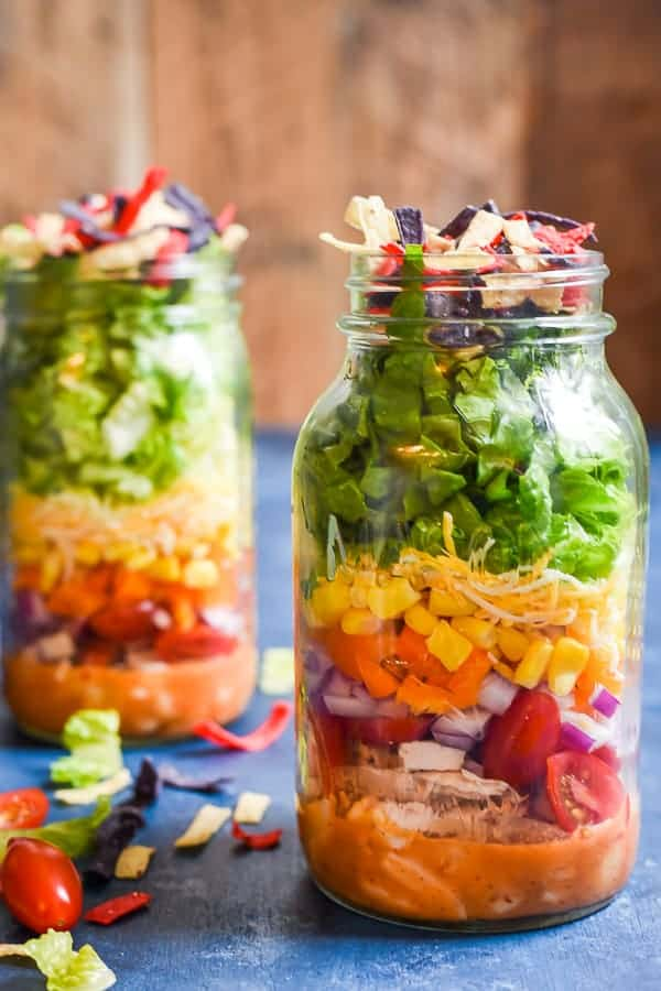 two mason jars filled with layers of lettuce, chicken, and vegetables