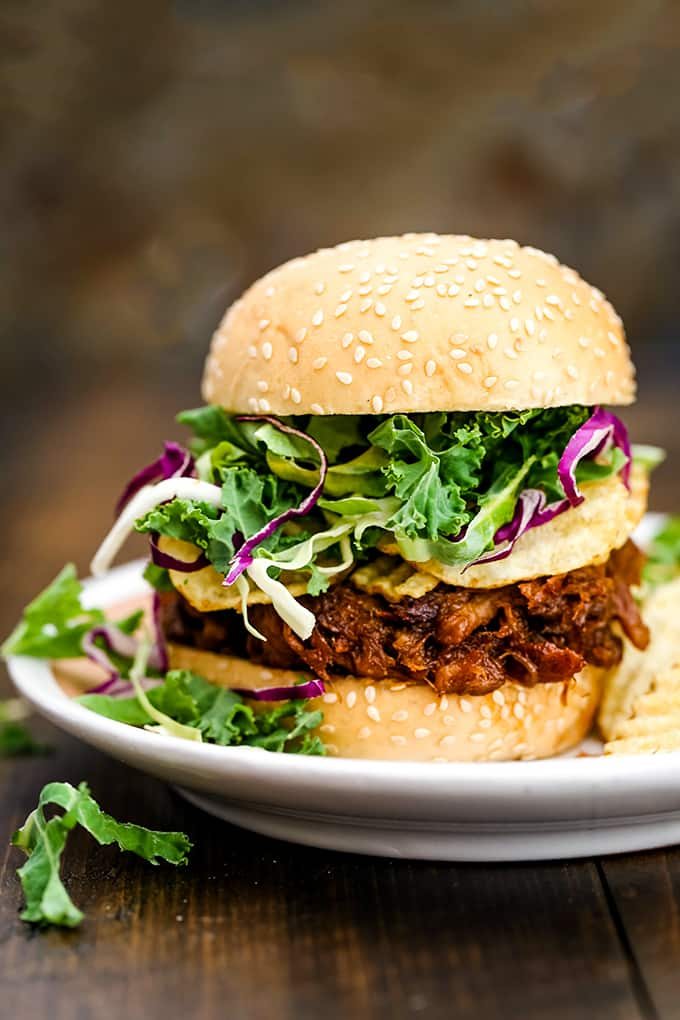 a pulled pork sandwich on a hamburger bun with lettuce and red onions