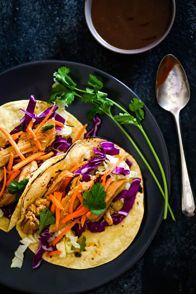two chicken tacos topped with carrots and red cabbage