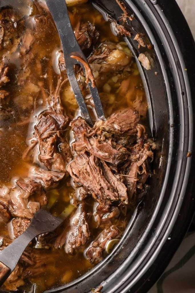 a slow cooker with shredded roast beef