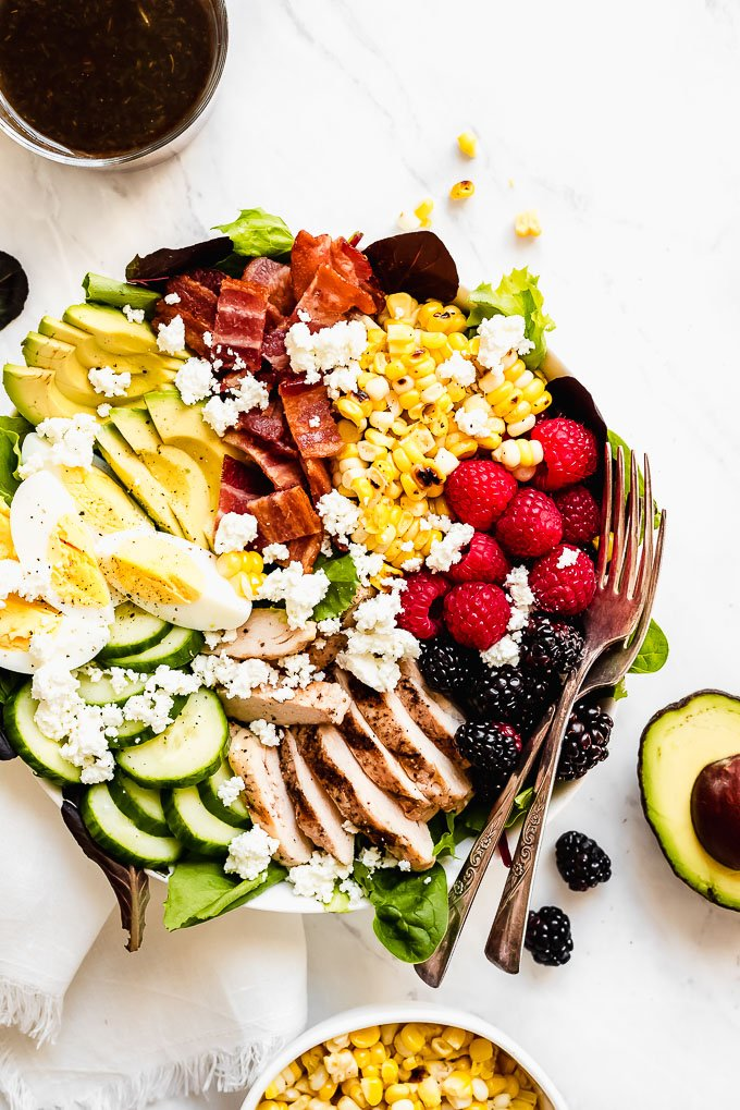 a plate of salad with corn, raspberries, blackberries, chicken, hard boiled eggs, bacon, and sliced cucumbers