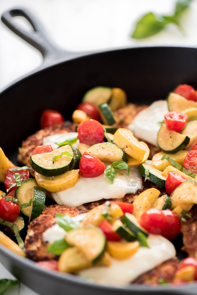 a skillet with summer squash, tomatoes, and chicken