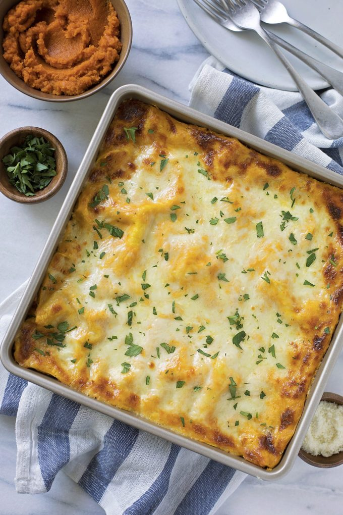 A baking dish with lasagna topped with white cheese and fresh herbs