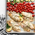 sheet pan with herb seasoned tilapia, cherry tomatoes, and green zucchini
