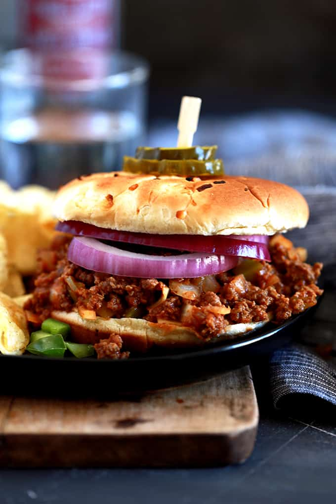 a sloppy joe with slices of red onion on a wooden board