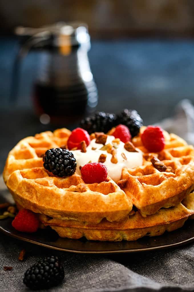 A stack of two Belgian waffles topped with vanilla yogurt, fresh blackberries, and raspberries