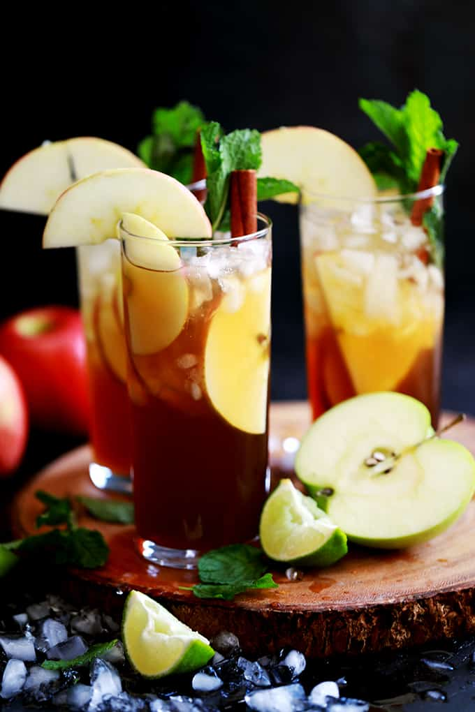 glasses of apple cider mojito with sliced apples and mint leaves on top