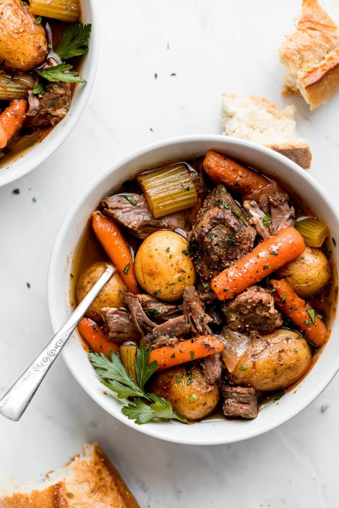 a white bowl of slow cooker beef stew with carrots, potatoes, celery, and chopped parsley