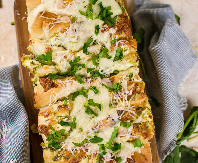 an flat lay image of pull apart spinach and artichoke bread on a wooden cutting board with parsley and grated cheese
