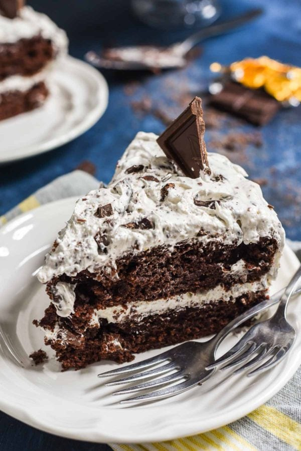 a chocolate layer cake with white filling and covered with oreo crumbs