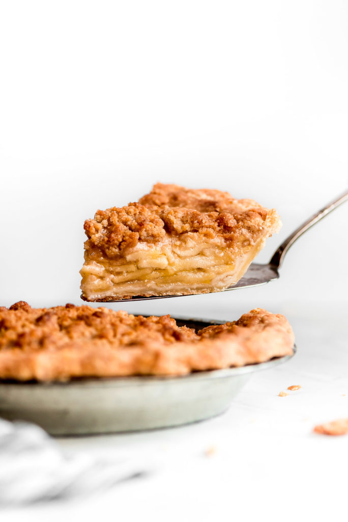 a wedge of homemade dutch apple pie with crispy topping and layers of sliced apples