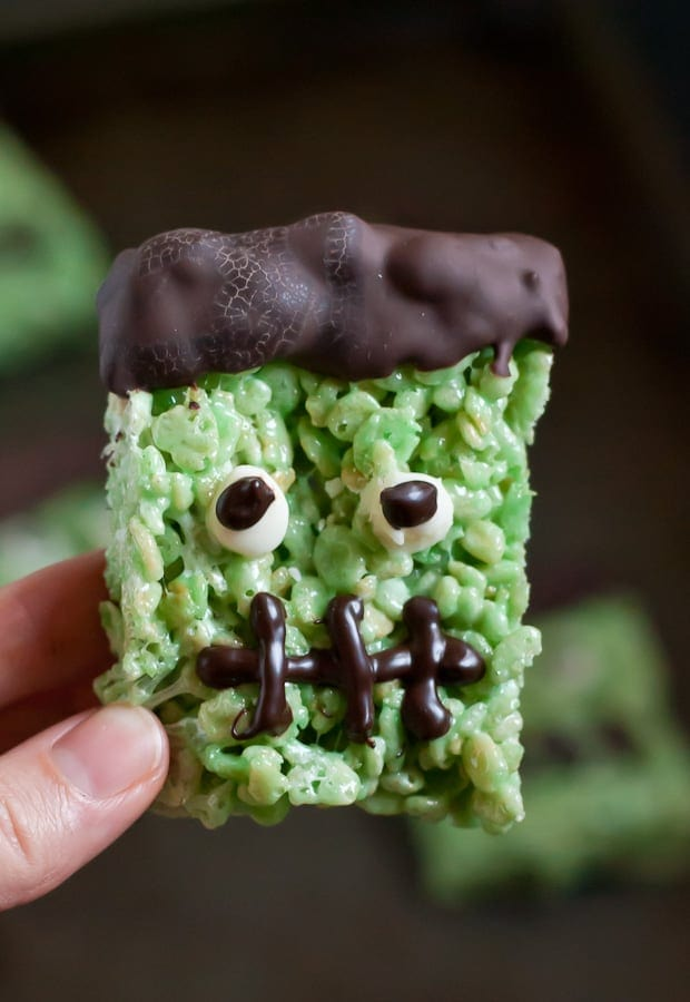 a green rice krispie treat with chocolate hair, google eyes, and a black mouth