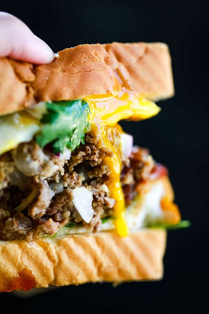 a close up image of a meatloaf sandwich with melted cheese, bacon, and arugula