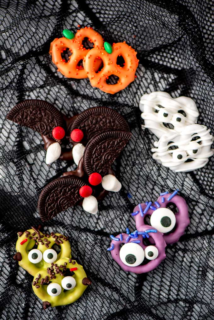 pretzels covered with purple, white, and orange chocolate and have google eyes to make them look like monsters, plus oreo bats