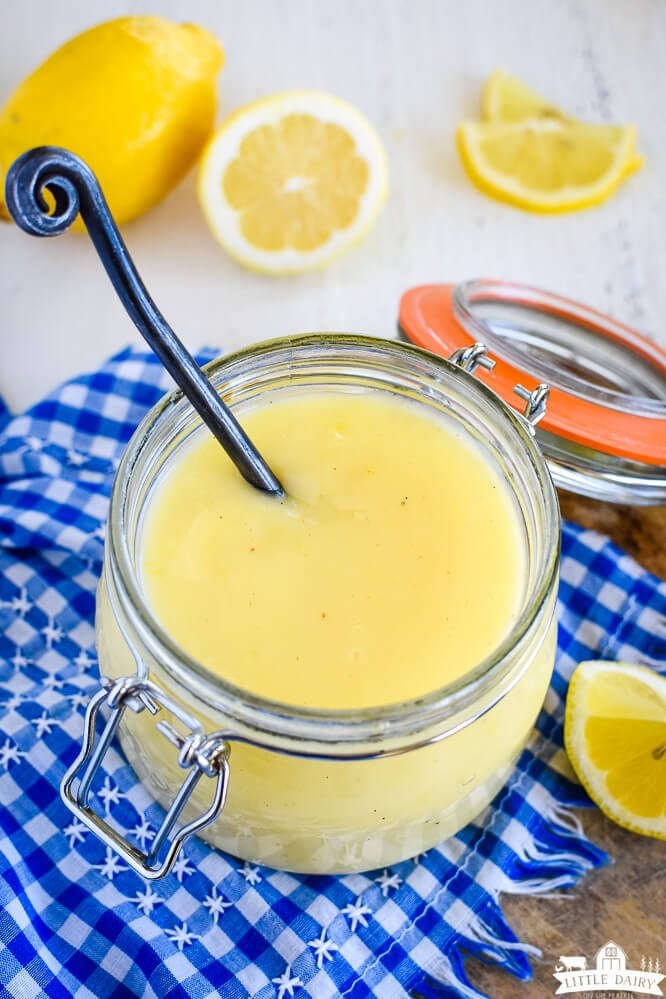 a jar of yellow dessert topping with a black spoon, on a blue and white gingham napkin, and fresh lemons in the background. Little Dairy on the Prairie