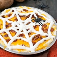 mashed potatoes topped with cheddar cheese, bacon bits, and a a sour cream spider web with a toy spider