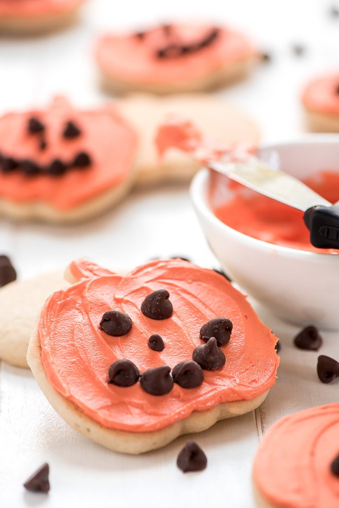 sugar cookies in the shape of a pumpkin with orange icing and a mouth, nose, and eyes made with chocolate chips