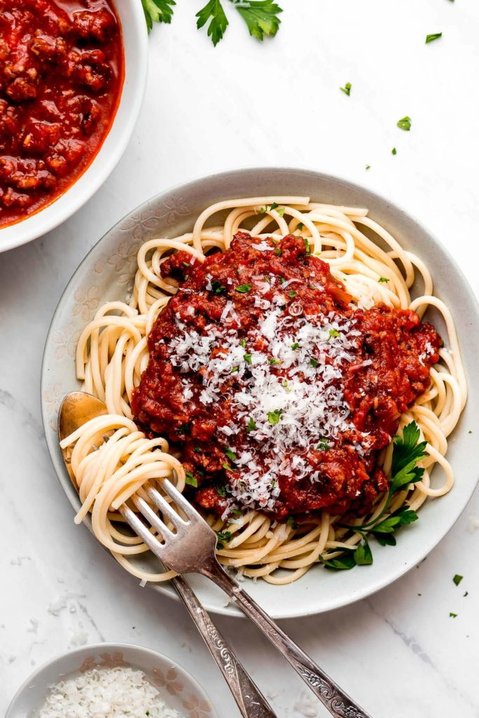 a white bowl filled with twirled spaghetti noodles topped with red ground beef spaghetti sauce, parmesan cheese, and chopped parsley