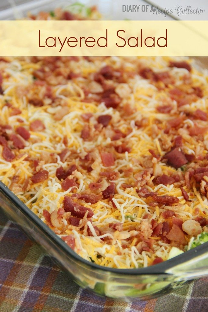 a baking pan with layered lettuce salad topped with shredded cheese and diced bacon