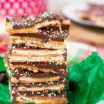 a stack of saltine cracker candy topped with chocolate and red, white, and green sprinkles