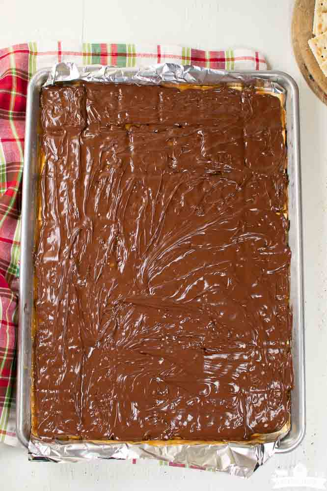a foil lined sheet pan with layers of saltine crackers, caramel, and melted chocolate