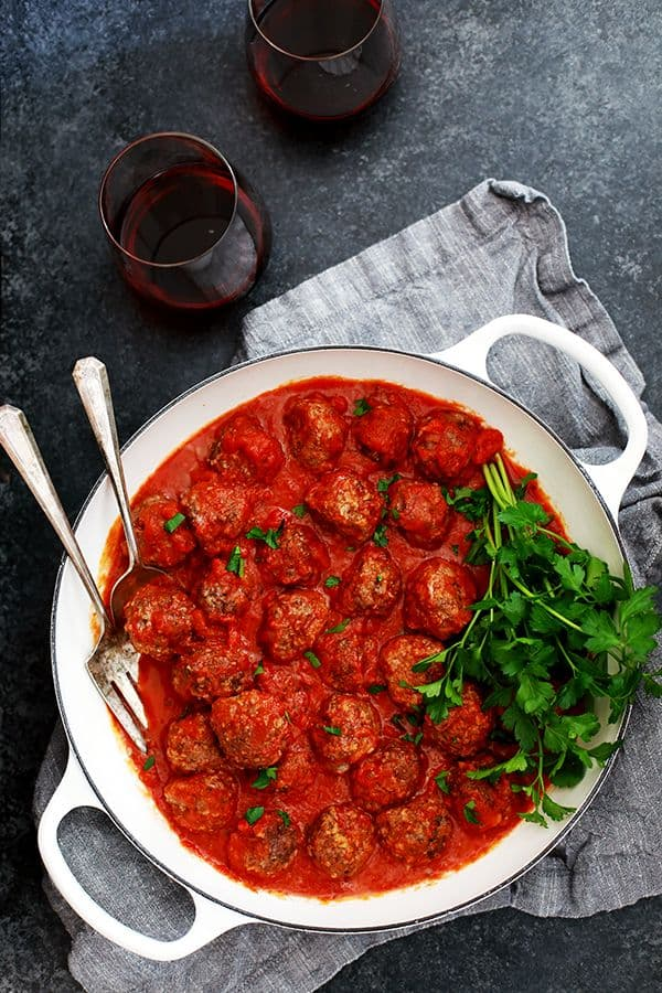 a white skillet with meatballs in red tomato sauce topped with parsley