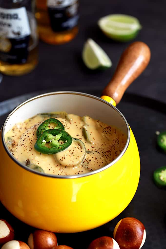 cheesy fondue topped with jalapenos in a bright yellow sauce pot with a wooden handle