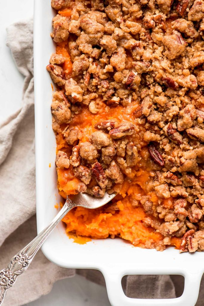 a white baking dish with mashed sweet potatoes topped with crispy pecan crumb topping