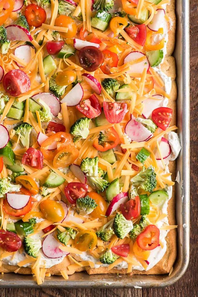 a sheet pan with cold pizza topped with chopped vegetables