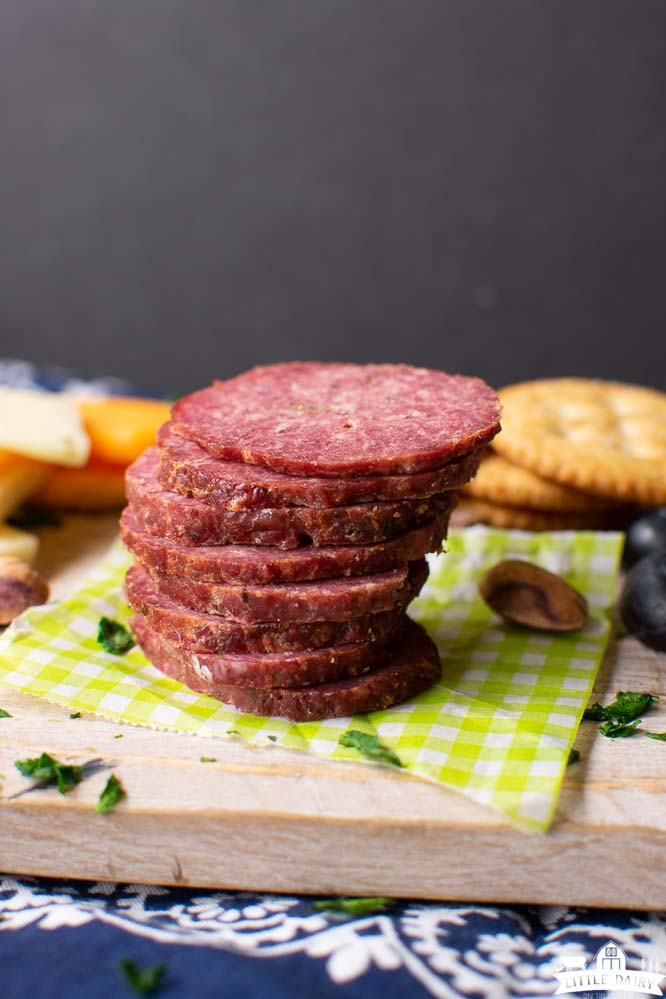 a stack of sliced summer sausage on a piece of green and white paper