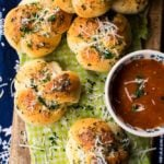 a wooden board with green and white checked piece of parchment paper with garlic knots topped with parmesan cheeseand marinara sauce
